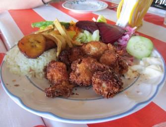 Crevettes panées à la chapelure de noix de coco râpée, patates et bananes plaintain frites, riz et crudités.