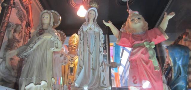 Dans une vitrine de centre commercial, à Xela (Guatémala), une statuette de Jean-Paul II derrière deux statuettes de la Vierge Marie.